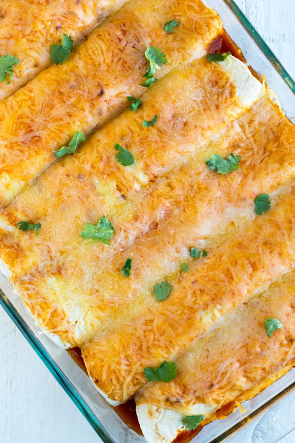 These easy chicken enchiladas are stuffed with slow roasted chicken and refried beans and topped with spicy enchilada sauce and melted cheese.
