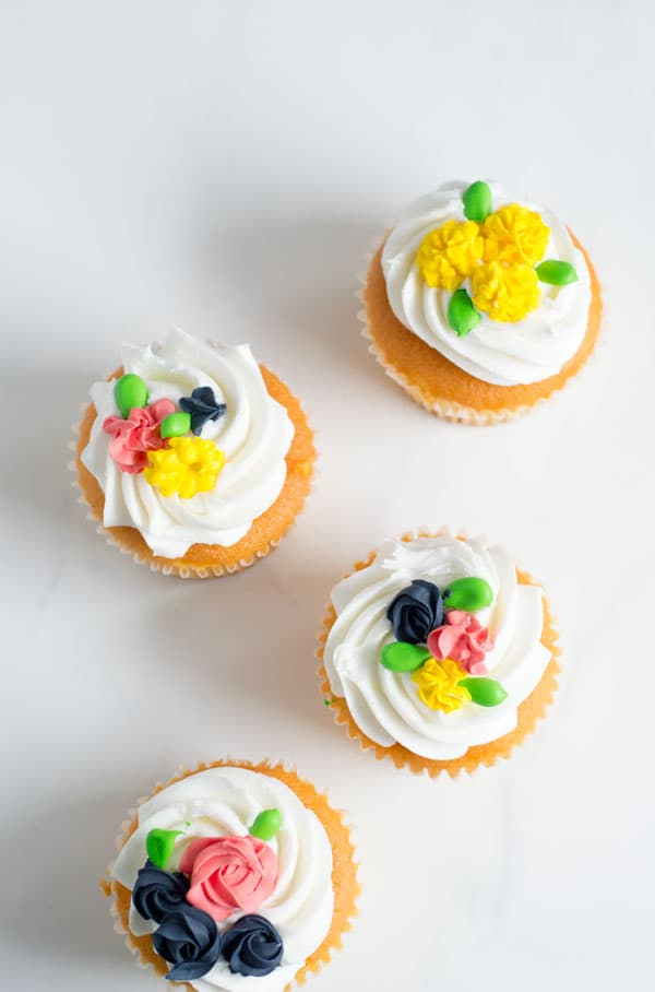 These simple royal icing flowers make great decorations for cakes, cupcakes, and cookies and are perfect for spring!