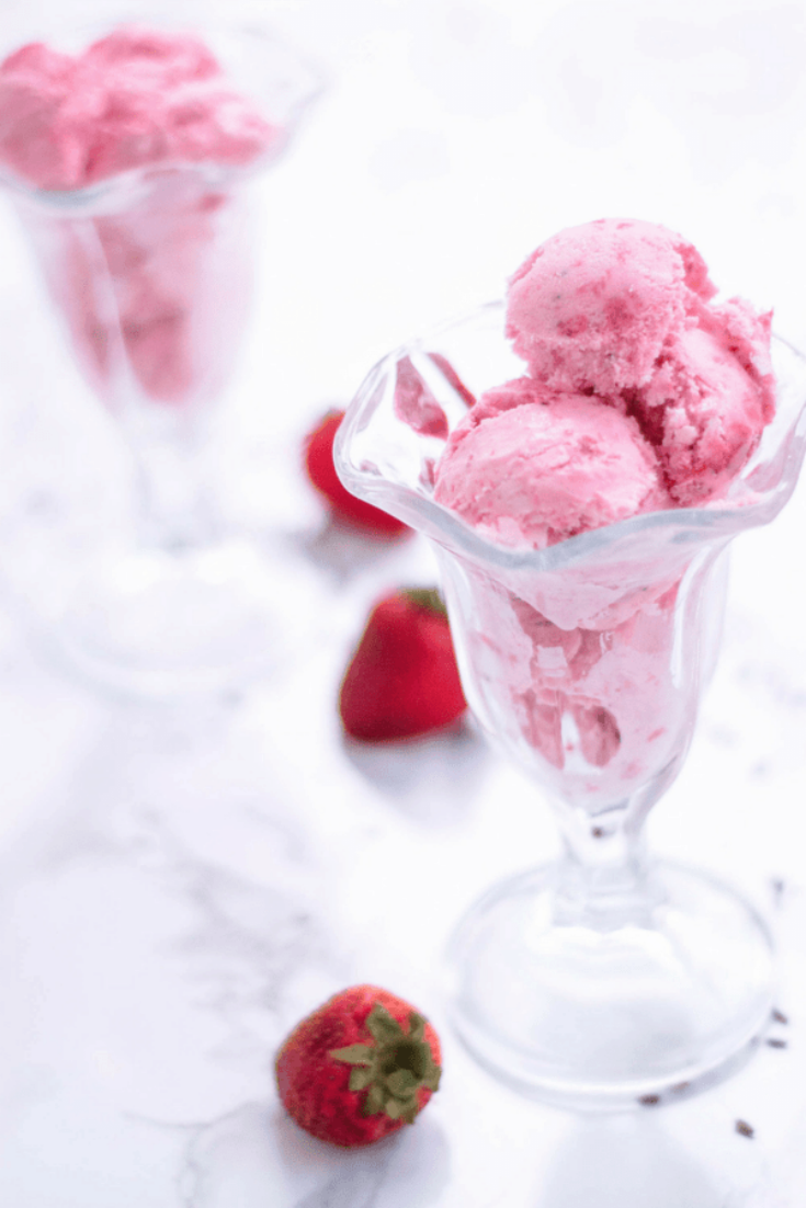 This homemade strawberry ice cream is creamy, dreamy, and made with fresh strawberries and  lavender blossoms. Looking for a healthy ice cream recipe for a sweet summer treat? Try churning this! It doesn't take much to learn how to make homemade ice cream. You can also switch out strawberries with blueberries based on your preference. #homemade #summerdessert #icecream #lavender #strawberry